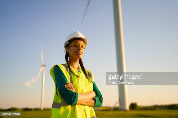 female engineer setting up wind turbine. - sustainable lifestyle stock pictures, royalty-free photos & images