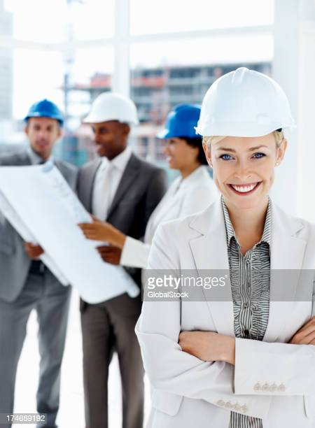 Female engineer smiling with colleagues in the background