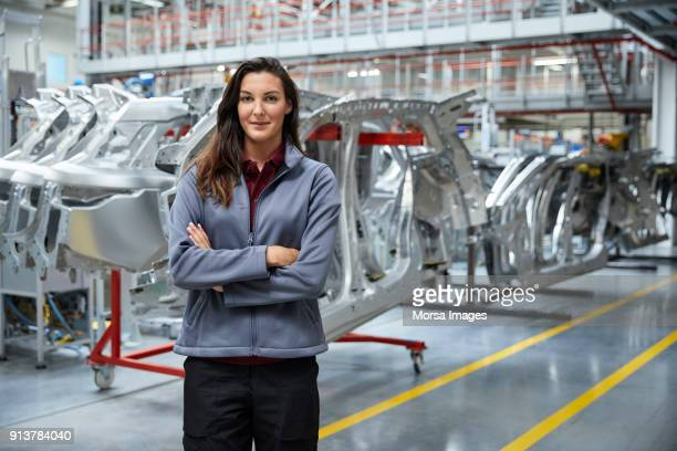 Female engineer standing against car chassis