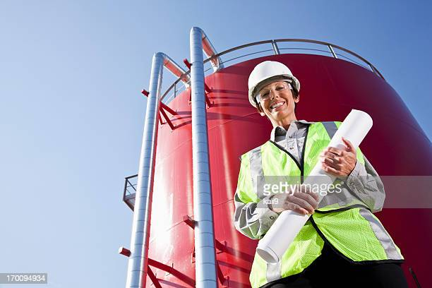 female engineer standing by industrial water tower - water tower storage tank stock pictures, royalty-free photos & images