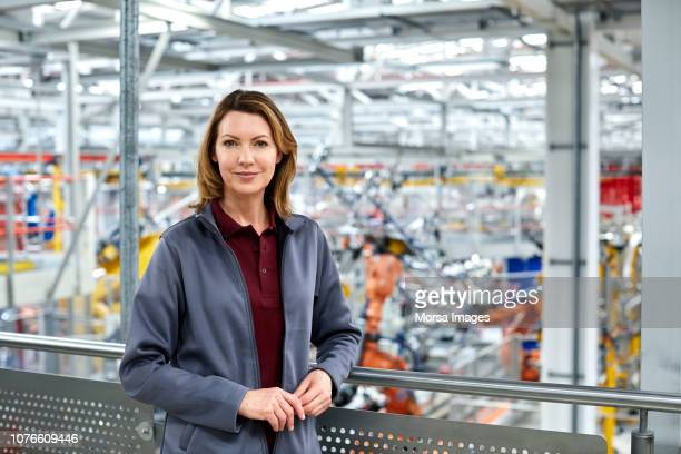 female engineer standing in automobile industry - leaning stock pictures, royalty-free photos & images