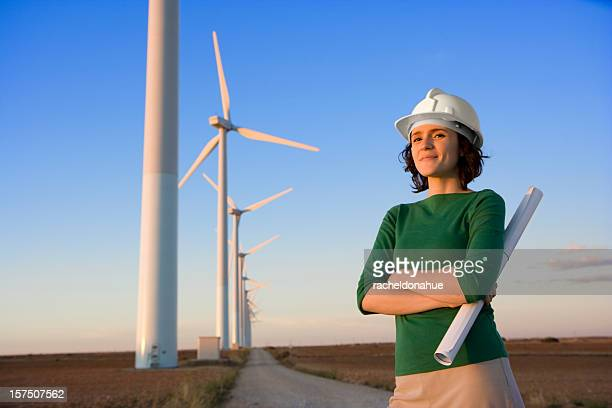 Female engineer stands in front of windmills