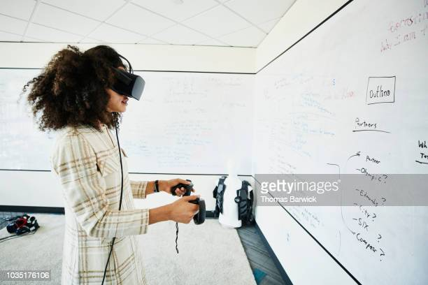 female engineer testing program on virtual reality headset in computer lab - simulatore di realtà virtuale foto e immagini stock