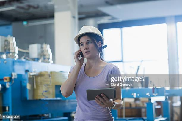 female engineer using a digital tablet and mobile phone in an industrial plant, freiburg im breisgau, baden-w��rttemberg, germany - sigrid gombert imagens e fotografias de stock