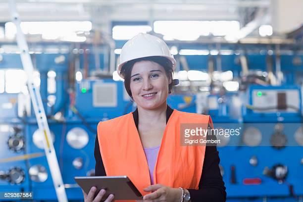 female engineer using a digital tablet in an industrial plant, freiburg im breisgau, baden-w��rttemberg, germany - sigrid gombert stockfoto's en -beelden