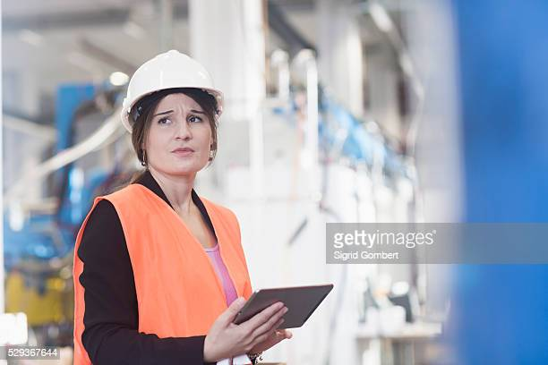 female engineer using a digital tablet in an industrial plant, freiburg im breisgau, baden-w��rttemberg, germany - sigrid gombert stock pictures, royalty-free photos & images