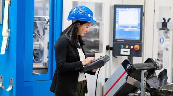 Female Engineer Using A Factory Remote Control System 1171979857