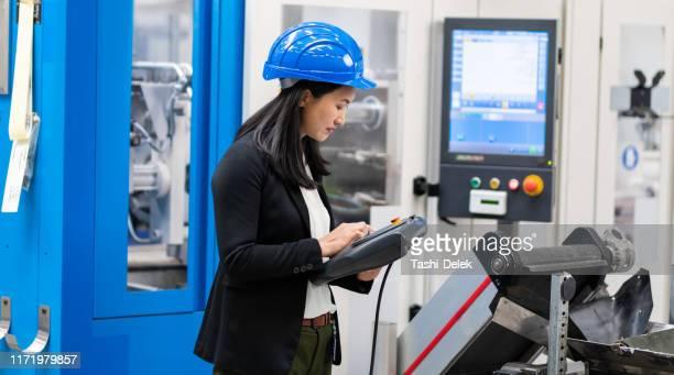 ingegnere donna che utilizza un sistema di controllo remoto di fabbrica - controllato a distanza foto e immagini stock
