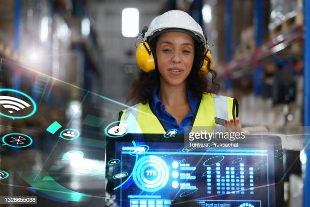 female engineer using computers to present graphs in a large modern warehouse. - revolution stock pictures, royalty-free photos & images