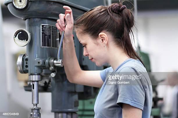 female engineer using machine in workshop - sigrid gombert stock-fotos und bilder