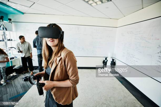 female engineer using virtual reality headset in computer lab - reforma assunto imagens e fotografias de stock