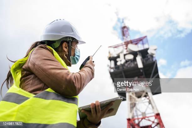 ingegnere donna che indossa una maschera protettiva per il viso durante la pandemia di covid-19. lavorare sul campo vicino a una torre di telecomunicazioni durante l'epidemia di coronavirus. - torre struttura edile foto e immagini stock