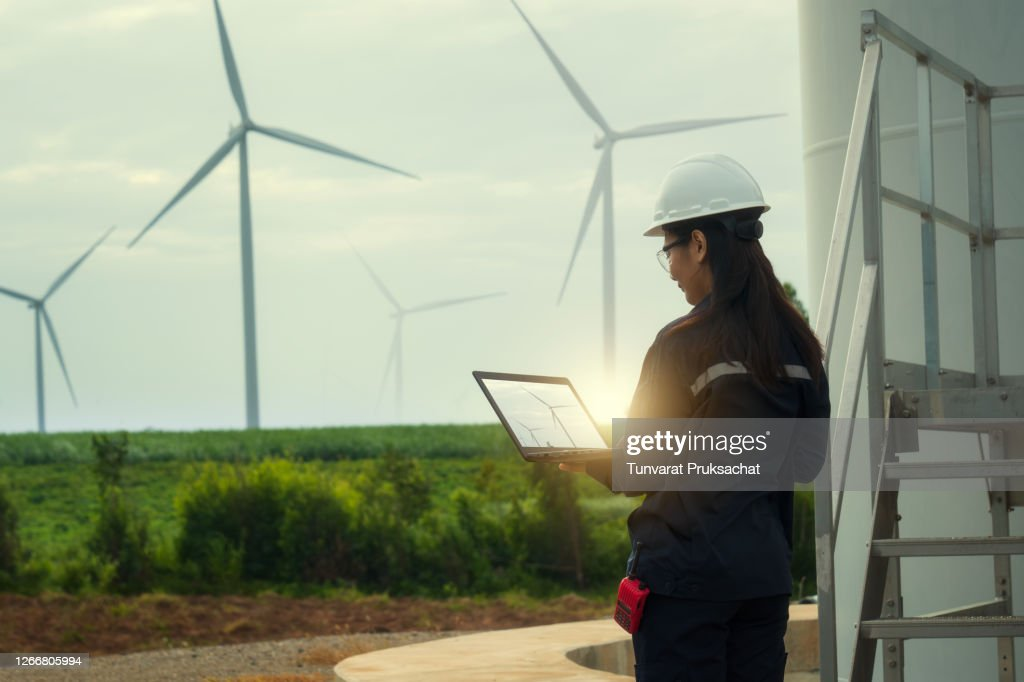 Female engineer wearing hard hat standing with digital tablet against wind turbine. : Stock Photo