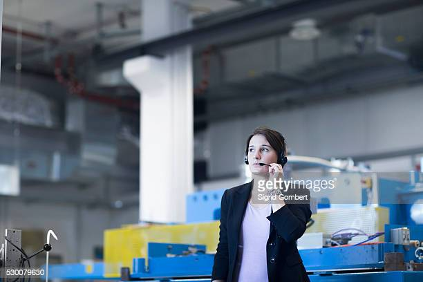 female engineer wearing headset in an industrial plant, freiburg im breisgau, baden-w��rttemberg, germany - sigrid gombert - fotografias e filmes do acervo