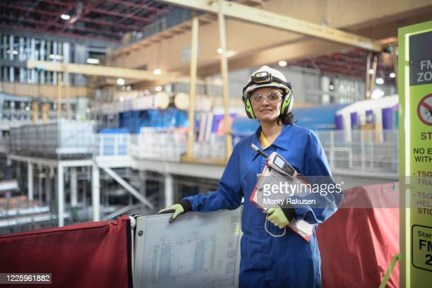 female engineer with a clipboard and electronic monitor at work in a nuclear power station. - atomic imagery stock pictures, royalty-free photos & images