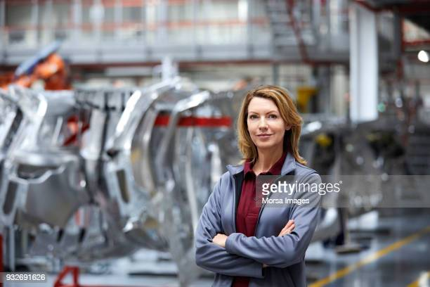 female engineer with arms crossed by car chassis - motor vehicle stock pictures, royalty-free photos & images