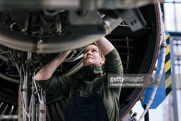 Female engineer working on jet engine