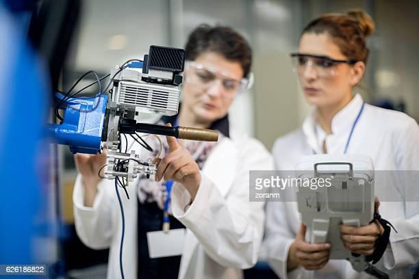 Female engineers conducting robotic arm