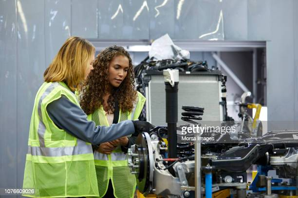 female engineers discussing over car chassis - mechanical engineering stock pictures, royalty-free photos & images