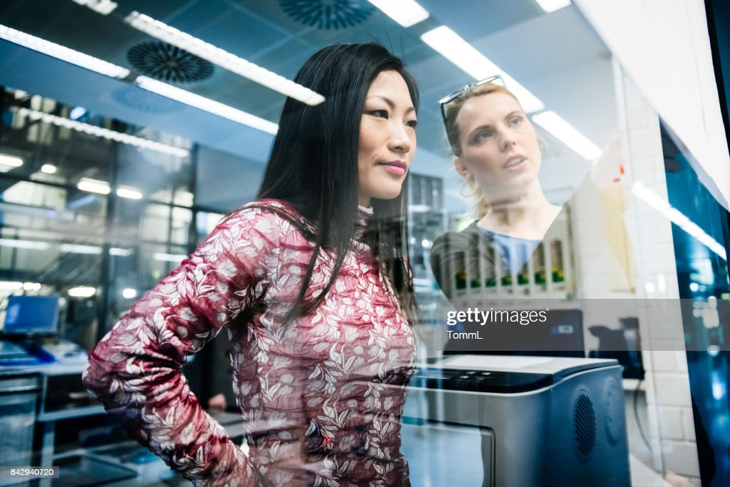 Two female engineers discussing a project in an industrial office while looking at documents pinned on a glass wall