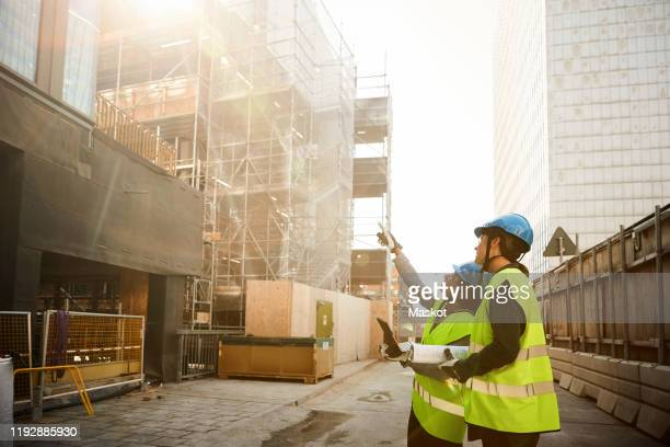 female engineers in reflective clothing discussing at construction site - construction site stock pictures, royalty-free photos & images