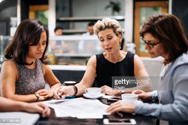 Female engineers looking at blueprint on the meeting