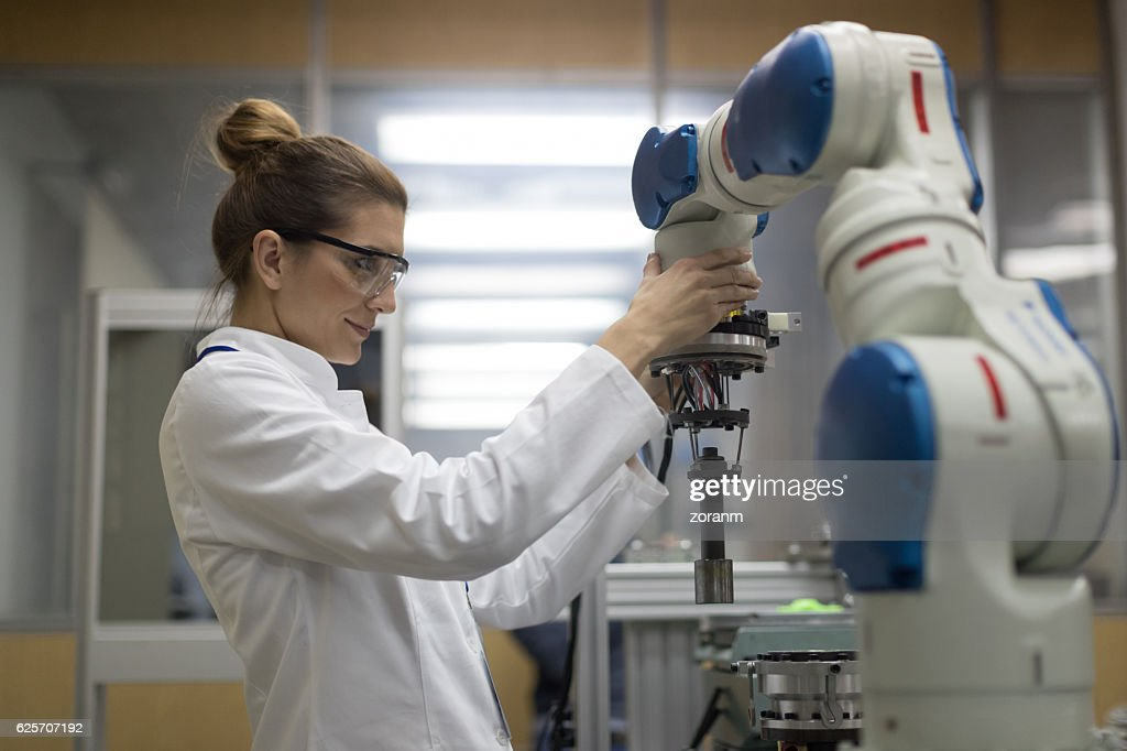 Female engineers working with robotic arm : Stock Photo