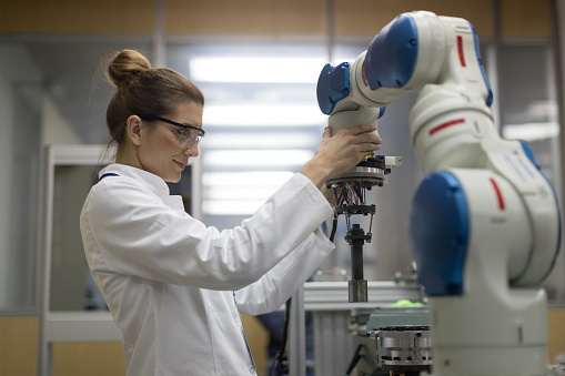 Female engineers working with robotic arm 625707192