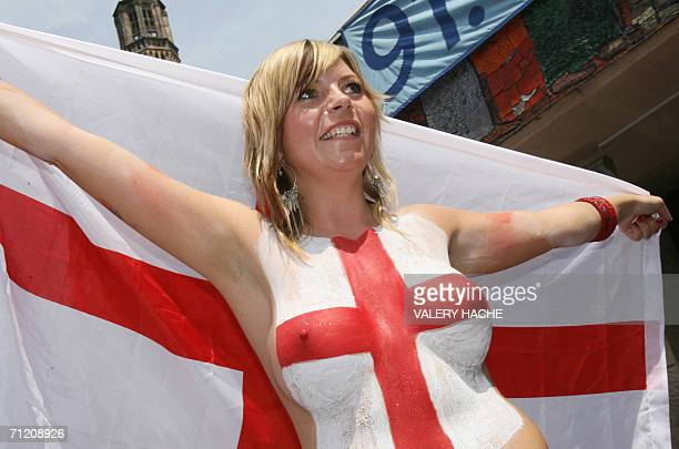 A female England supporter who has painted her naked bust with the colours of the St George's flag dances on a table of a cafe in the center of...