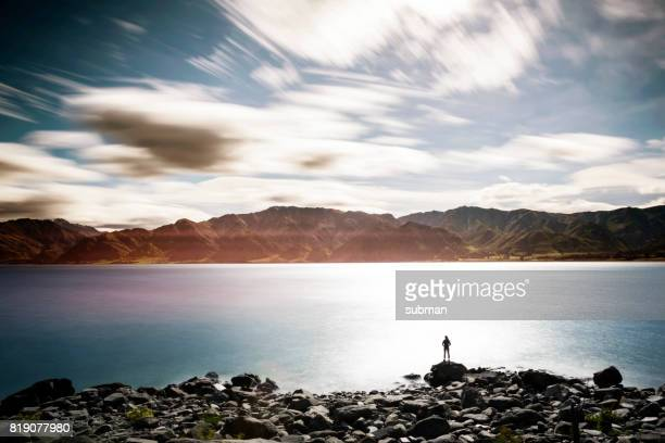 female enjoying the view from the side of the lake - landscape scenery stock photos and pictures