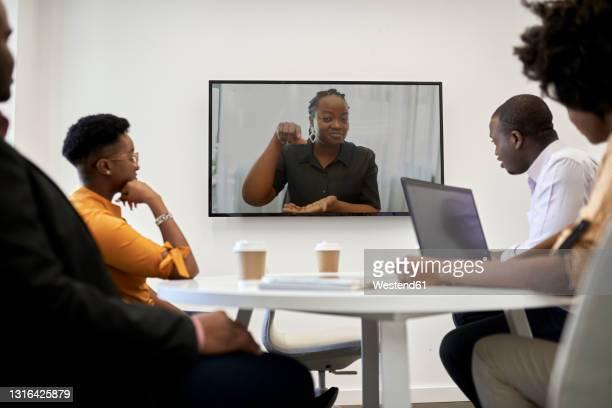 female entrepreneur gesturing during video conference at office - flexplekken stockfoto's en -beelden