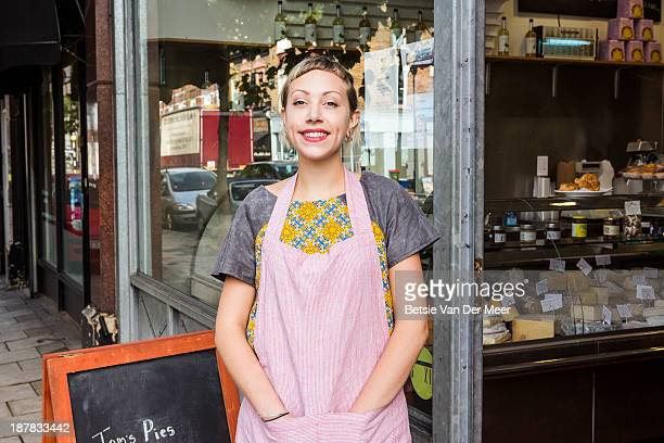 female entrepreneur in front of deli shop.