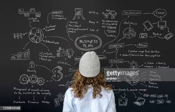 female entrepreneur looking at the business plan on a blackboard - business plan stock pictures, royalty-free photos & images