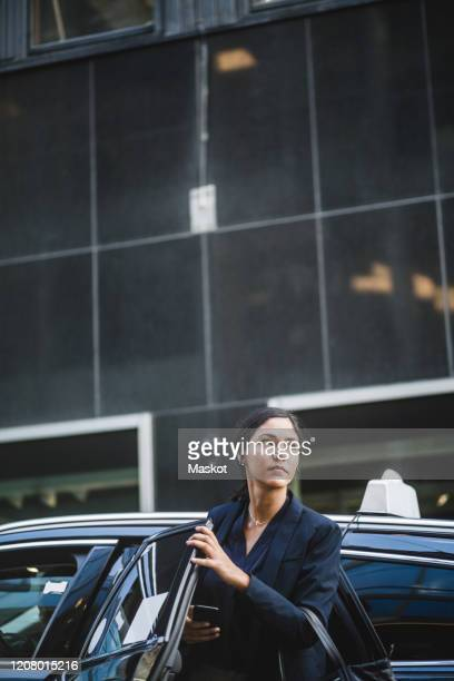 female entrepreneur looking away while coming out from car - 降り立つ ストックフォトと画像