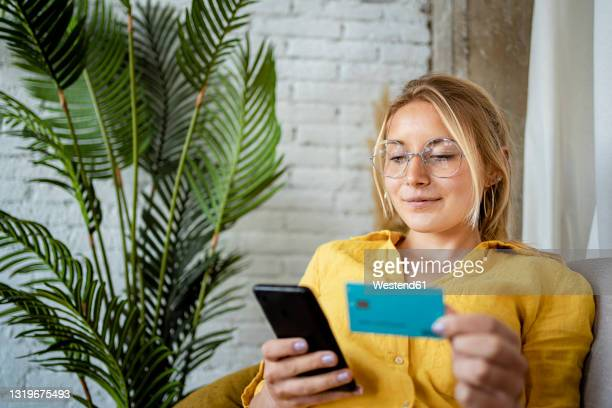 female entrepreneur making online payment through credit card at home - bank stock pictures, royalty-free photos & images