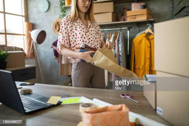 female entrepreneur preparing new orders for online customers - roupa de mulher imagens e fotografias de stock