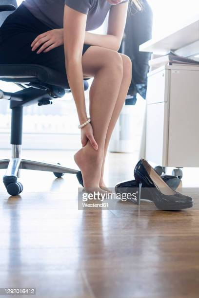 female entrepreneur rubbing feet while sitting on chair in office - high heels stock pictures, royalty-free photos & images