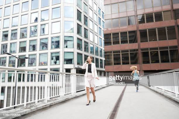 female entrepreneur talking through mobile phone while woman jogging on footbridge in financial district - entrepreneur stock pictures, royalty-free photos & images