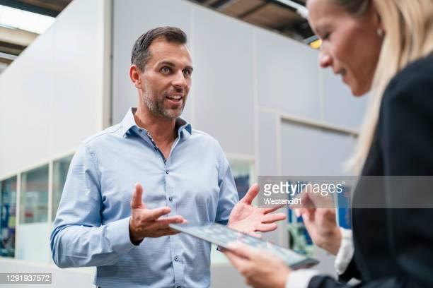 female entrepreneur using digital tablet while male colleague explaining standing in industry - expliquer photos et images de collection