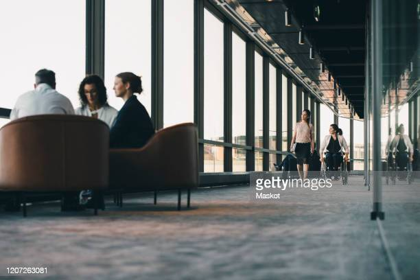 female entrepreneur walking with disabled colleague while business executives discussing in background at workplace - disabilitycollection stock-fotos und bilder