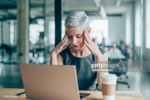 female entrepreneur with headache sitting at desk - struggle stock pictures, royalty-free photos & images