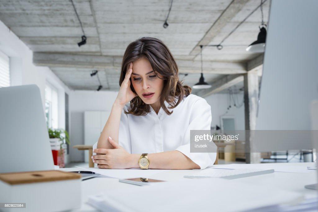 机に座って頭痛女性起業家 : ストックフォト