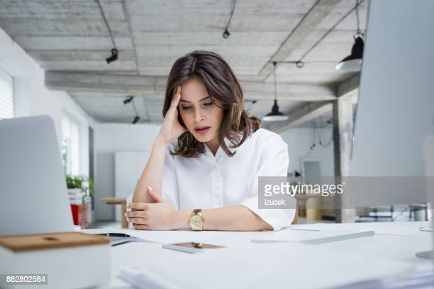 Female entrepreneur with headache sitting at desk