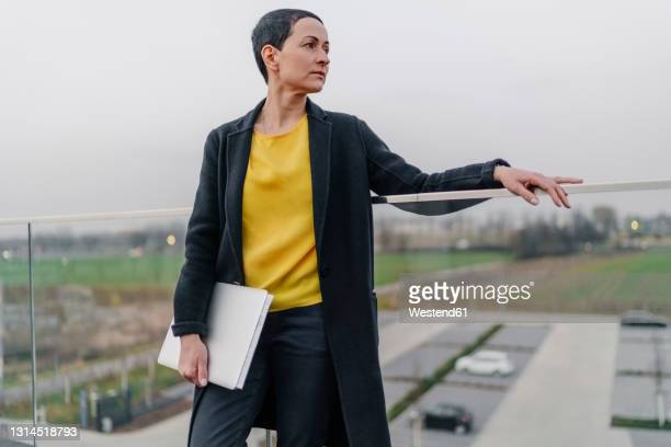 female entrepreneur with laptop looking away while leaning on railing against sky - coat stock pictures, royalty-free photos & images
