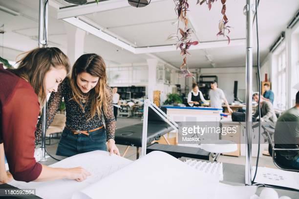 female entrepreneurs discussing over paper at table in creative office - agence de design photos et images de collection