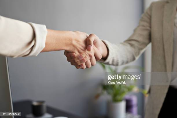 female entrepreneurs shaking hands at workplace - employee engagement stock pictures, royalty-free photos & images