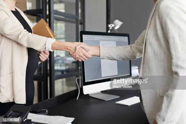 female entrepreneurs shaking hands in office - cream coloured blazer stock pictures, royalty-free photos & images
