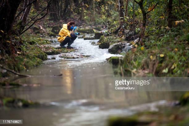 female environmental researcher taking a stream water sample - biologo foto e immagini stock