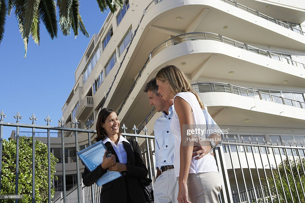 Female Estate Agent Shows a Couple a Block of Apartments : Stock Photo