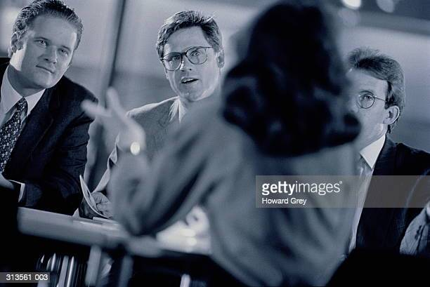 Female executive addressing three male colleagues in meeting (B&W)